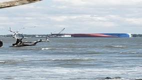 Salvage crews work to remove fuel from capsized ship