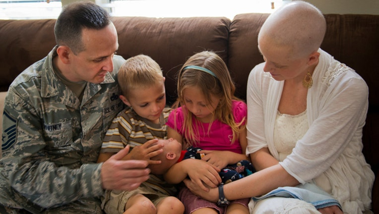 Father, mother battling cancer, and kids look over newborn baby-401385