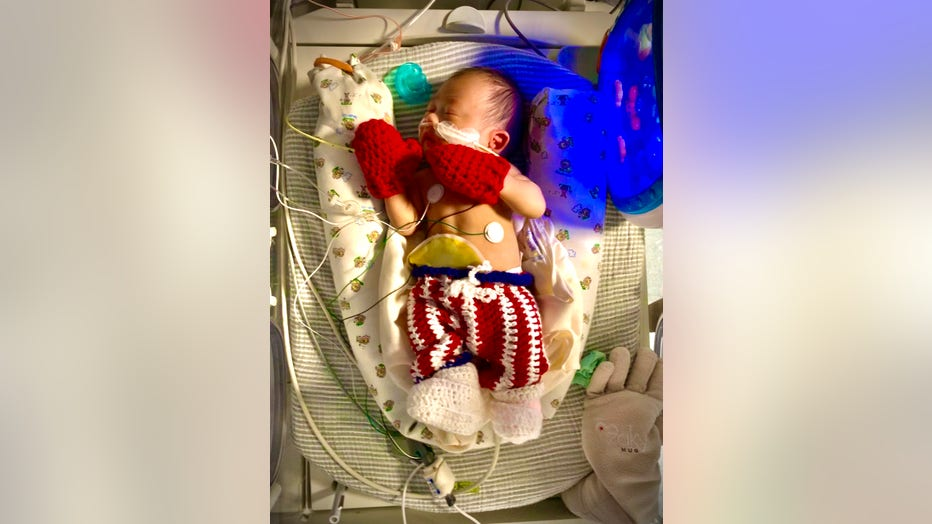 NICU baby dressed as Rocky Balboa, with crocheted boxing shorts and tiny red boxing mits.