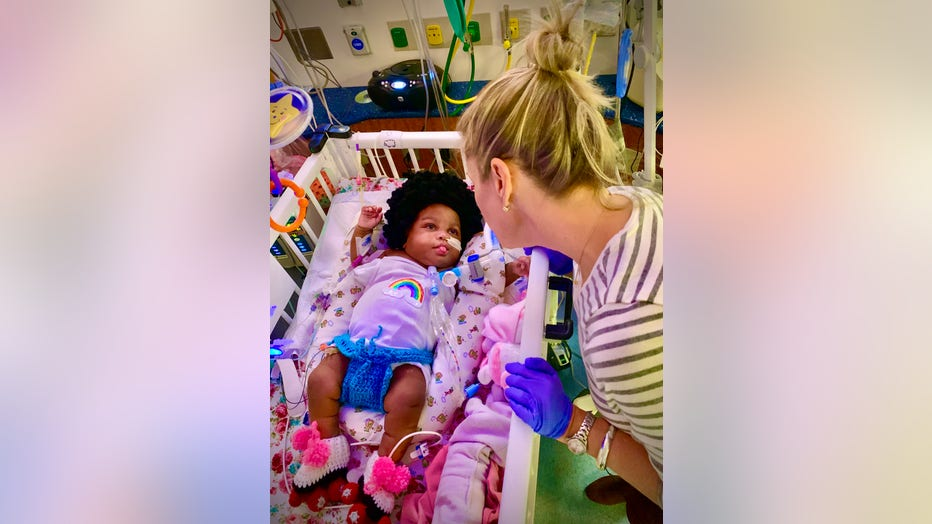 Children's Healthcare of Atlanta NICU nurse leans over baby dressed up as a