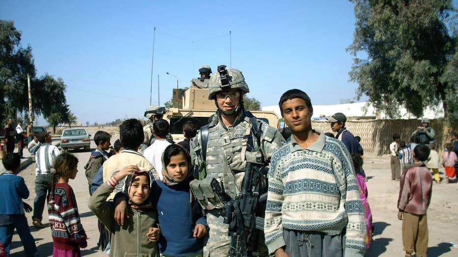 Garrett Cathcart poses with children in Iraq in 2006.