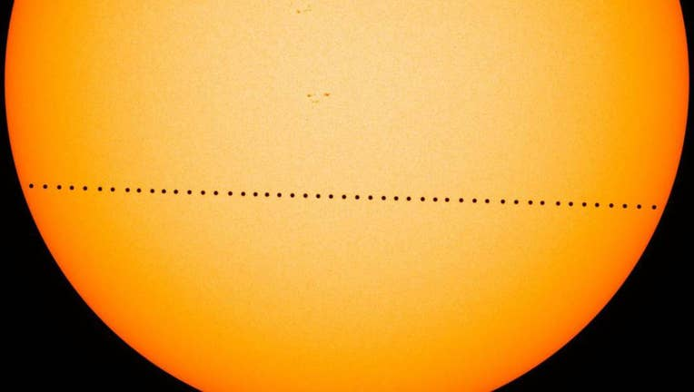 The black dot of Mercury crosses the sun's disk in a composite image made during the last Mercury transit in 2016. Photo via NASA.