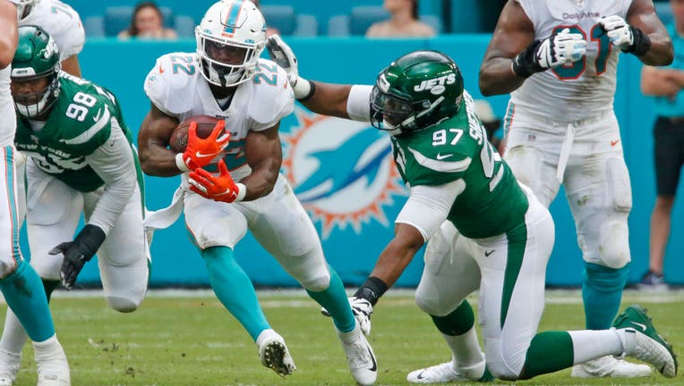 Mark Walton #22 of the Miami Dolphins runs past the attempted tackle of Nathan Shepherd #97 of the New York Jets during an NFL game on November 3, 2019 at Hard Rock Stadium in Miami Gardens, Florida. (Photo by Joel Auerbach/Getty Images)