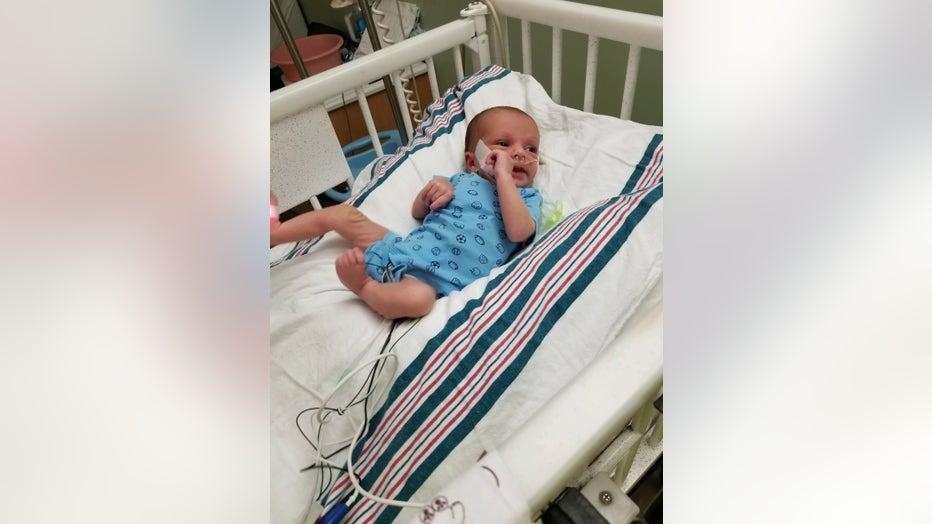 Baby lies in a hospital crib