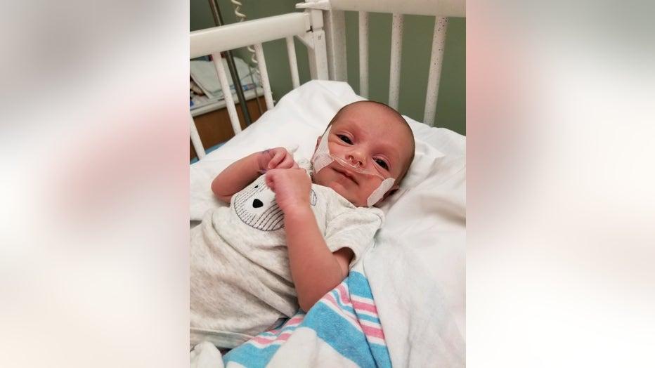 Baby lies in hospital crib