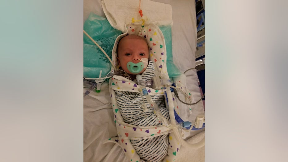 Baby lies swaddled in hospital bed.