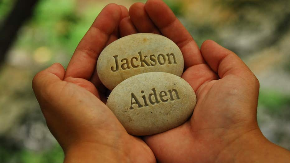 Hands hold stones carved with the names of couple's twin boys