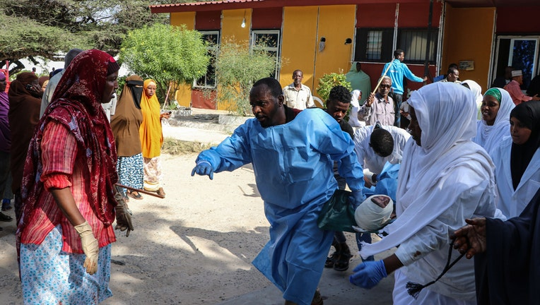 Nurses carry a person, that was wounded during a car bombing attack, at the Madina Hospital in Mogadishu, on December 28, 2019.