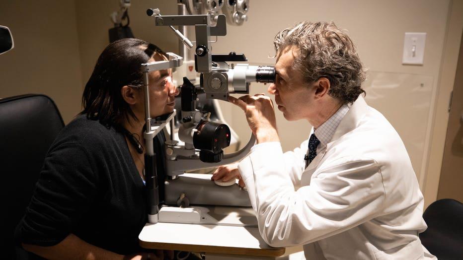Eye surgeon checks woman's vision