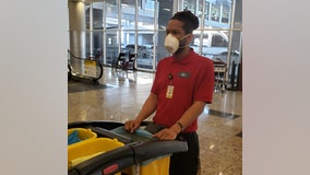 Workers, airport travelers don masks out of concerns about deadly coronavirus