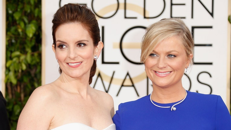 Hosts Tina Fey (L) and Amy Poehler attend the 72nd Annual Golden Globe Awards at The Beverly Hilton Hotel on January 11, 2015 in Beverly Hills, California.