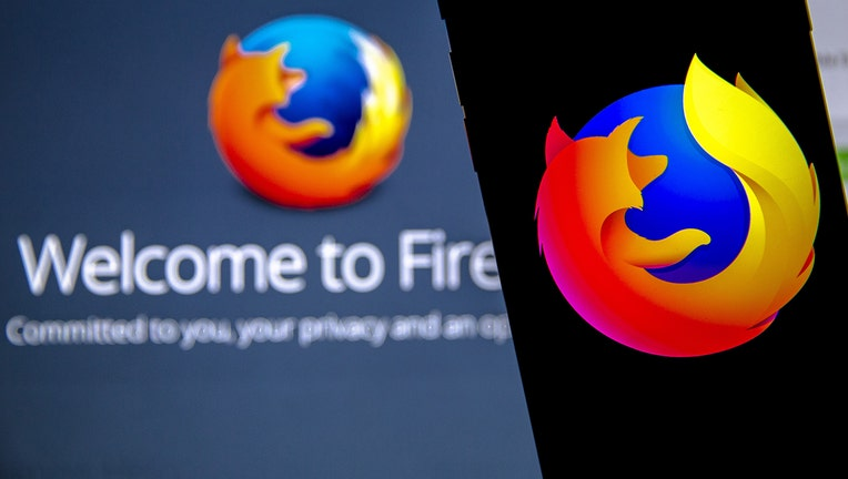 Mozilla Firefox logos are seen displayed on a laptop and phone screen. (Photo by Ali Balikci/Anadolu Agency/Getty Images)