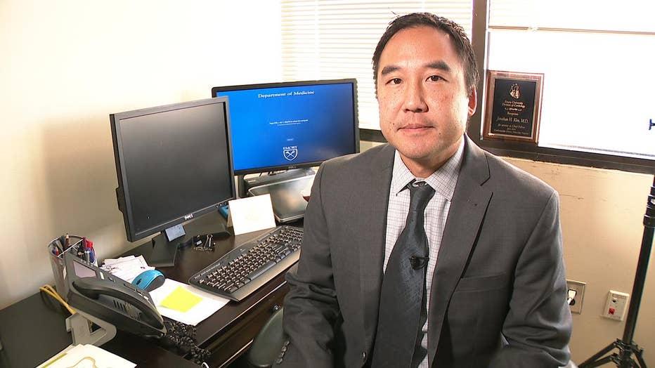 Dr. Jonathan Kim sits at his desk.
