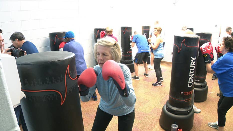 Woman in boxing gloves stands in front of punching bag.