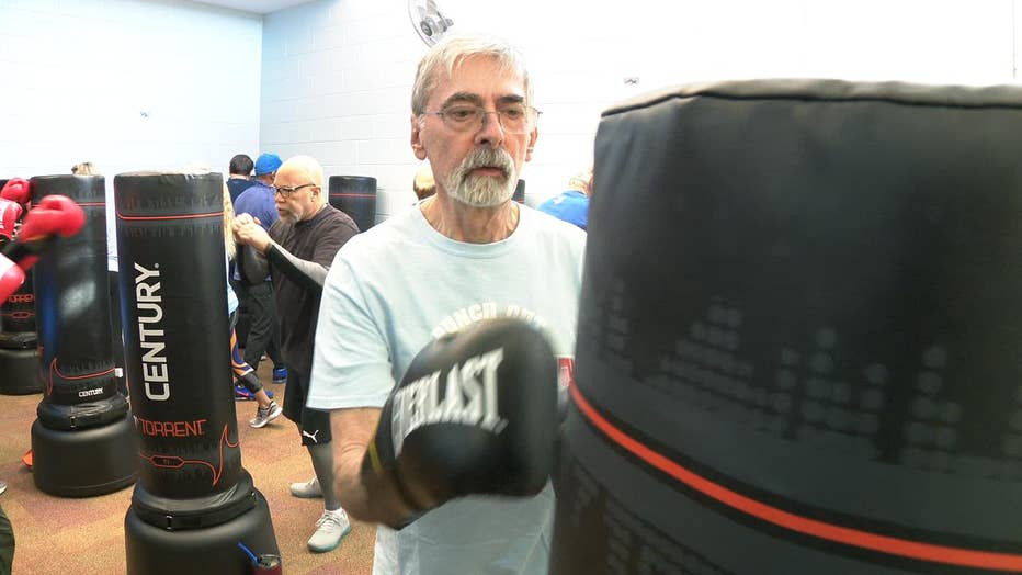 Man wearing boxing gloves punches bag