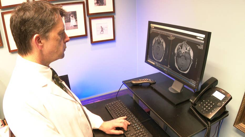 Doctor looks at images of patient's brain.