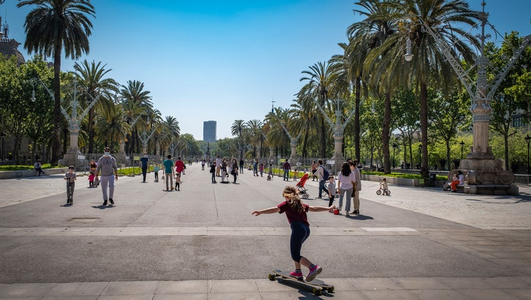 A girl plays with a skateboard during the first day of