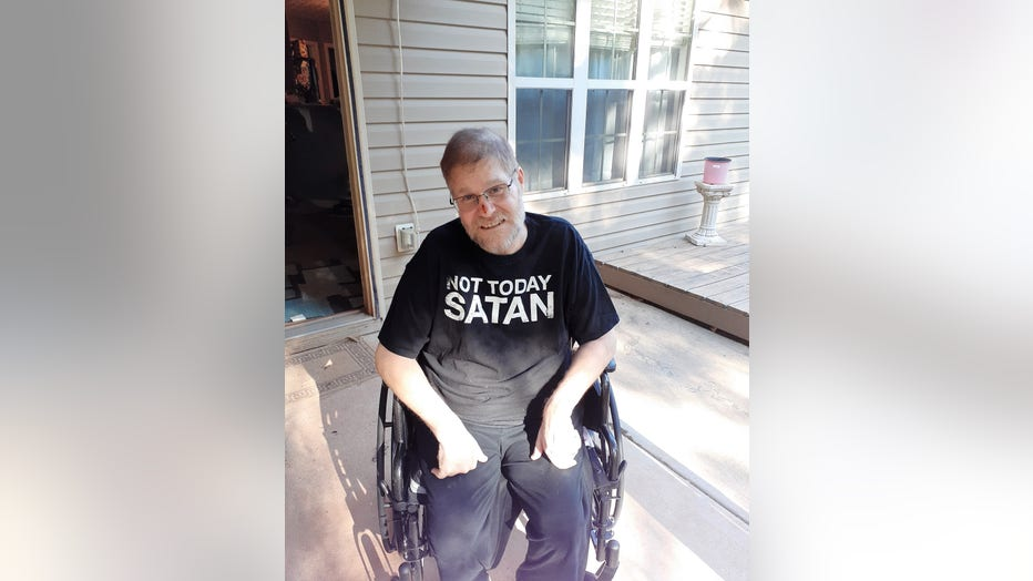 Man in wheelchair sits on front porch, smiling and wearing a t-shirt that reads