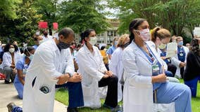Emory health care workers kneel in a show of solidarity