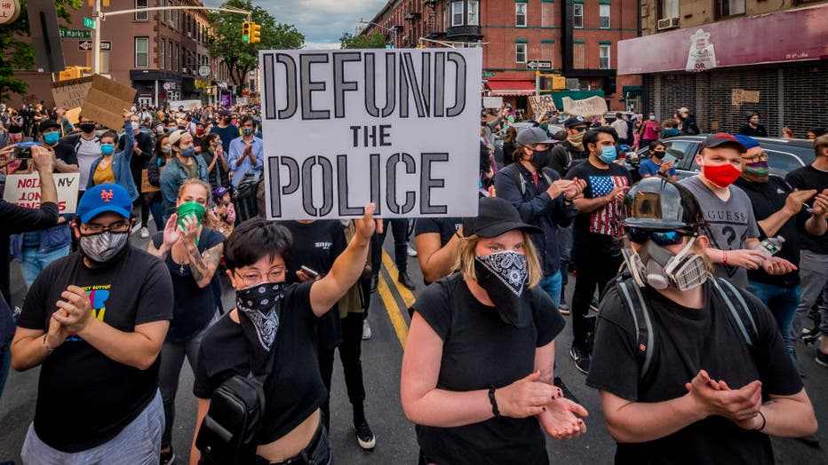 1b2a6905-A participant holding a Defund The Police sign at the