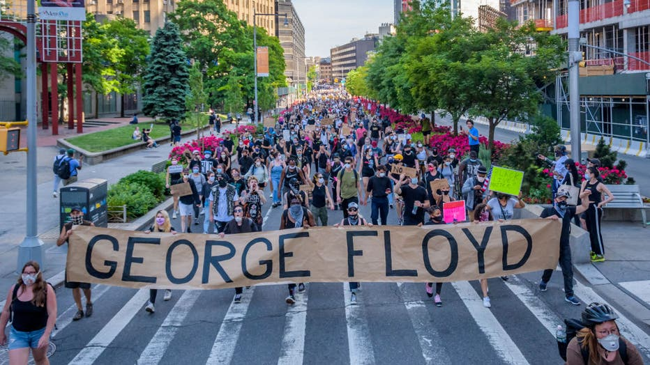 Protesters holding a giant banner reading GEORGE FLOYD at
