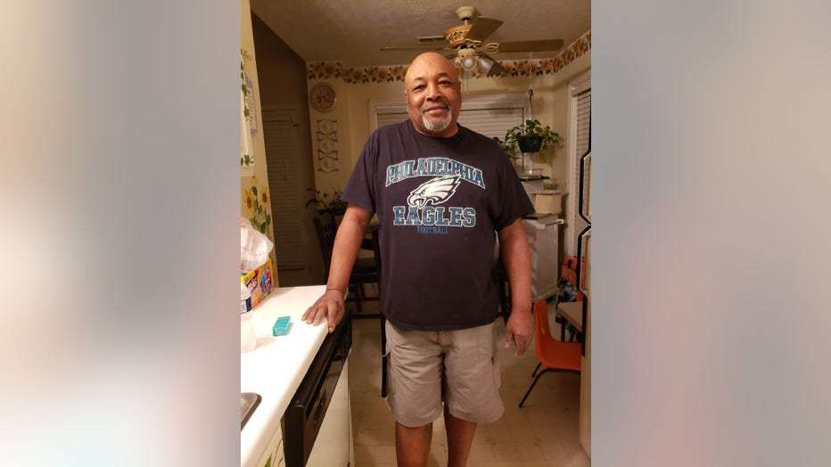 Man leans against kitchen counter. He is smiling and wearing a Philadelphia Eagles t-shirt