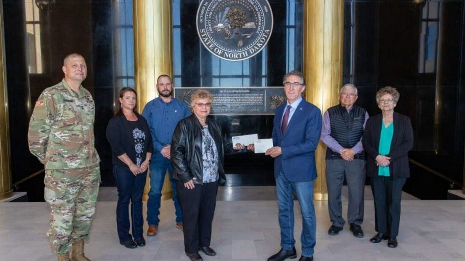 North Dakota Gov. Doug Burgum presents Ron Hepper's military ID tag to his widow, Ruth Hepper Wednesday at the Capitol in Bismarck. Also pictured are (from left) Maj. Gen. Al Dohrmann, Hepper's daughter Julie Hornbacher and her husband, Jim, and Ron Hepper's brother Stanley Hepper and his wife, Kathleen. (Office of Gov. Doug Burgum)