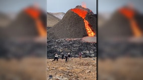 People play volleyball in front of erupting volcano in Iceland