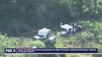 Man charged with murder after men found burned in truck