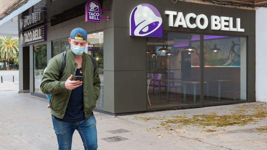A man wearing a face mask walks past a fast food restaurant