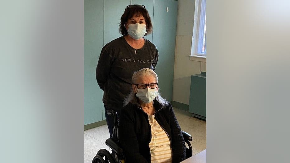Woman in mask stands behind her elderly mother, who is in a wheelchair.