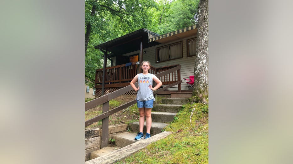 """Young girls stands on steps outside her summer camp. She is wearing a t-shirt that says """"camp"""" and is smiling, with her hands on her hips. She looks happy."""