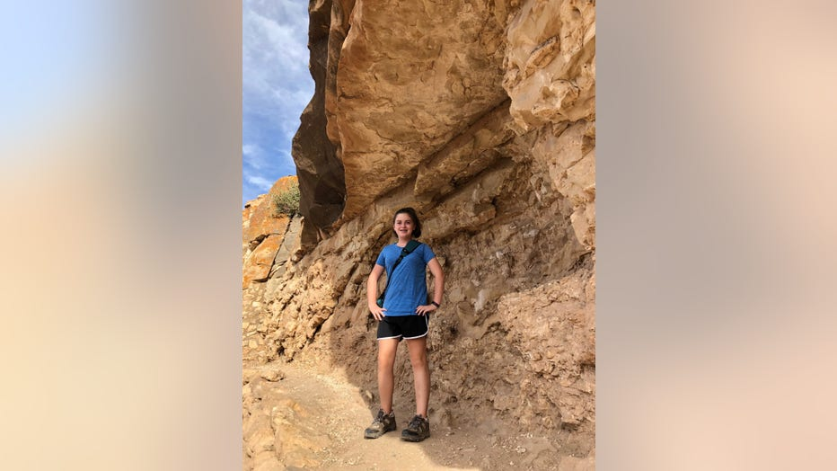 Young girl stands in front of rock formation with her hands on her hips. She is wearing shorts and a t-shirt and is smiling at the camera.