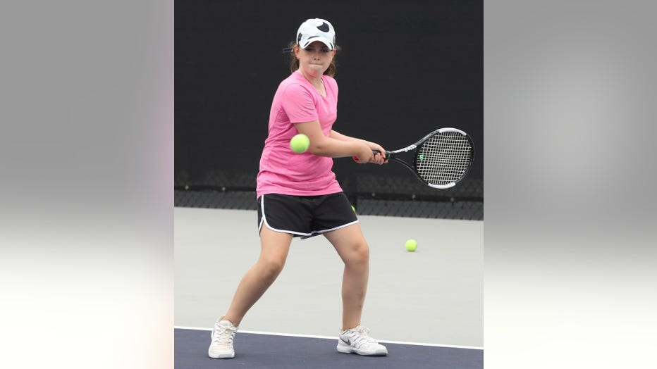 Girl in baseball hat swings a tennis racket at a ball.
