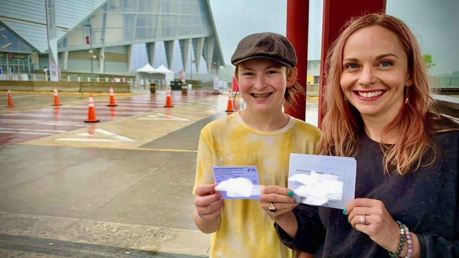 Teen boy wearing cap poses with his mother, both of them holding their COVID-19 vaccine cards, outside Atlanta's Mercedes-Benz Stadium.