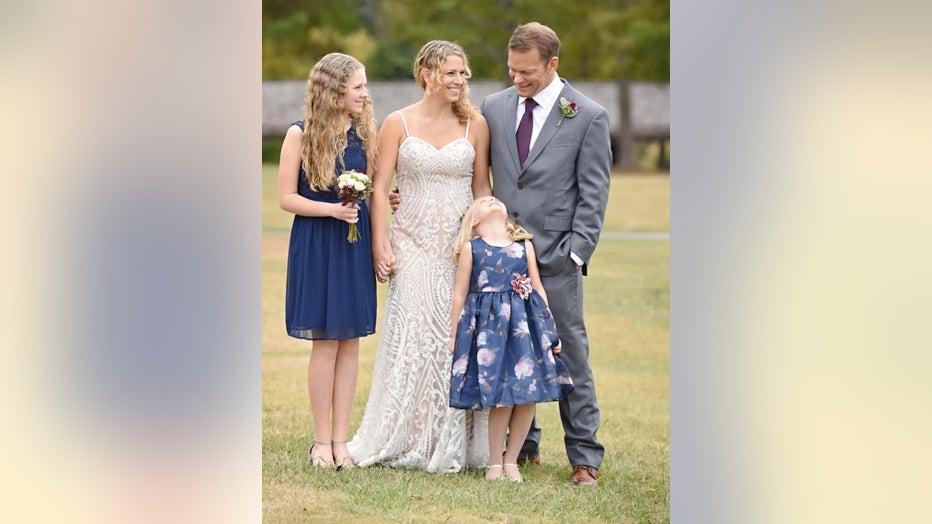 Couple in wedding attire pose with their children.
