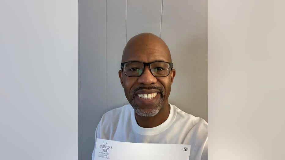 Smiling man with dark skin and shaved head holds a white envelope from RIP Medical Debt.