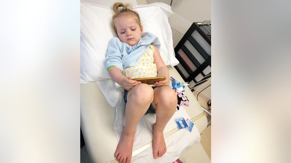 Little girl lies on an exam table playing on a cellphone. She has just received a shot.