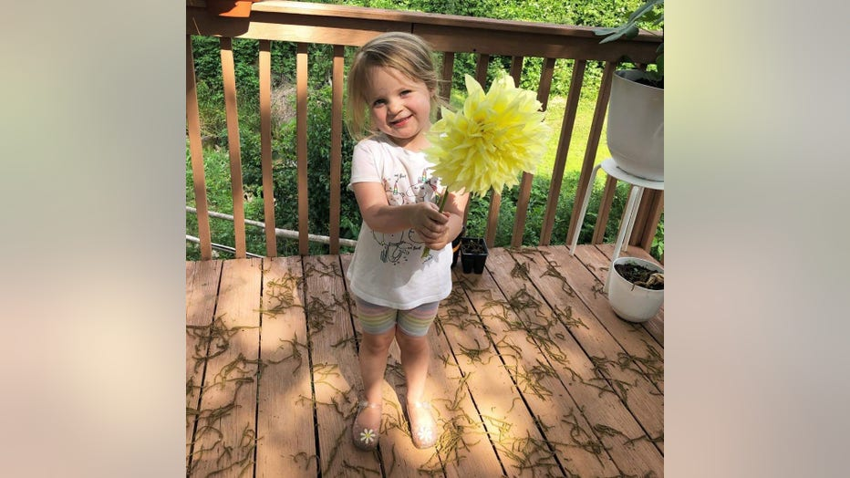 Little blonde girl holds a giant yellow flower up to the camera. She is 3 and smiling.