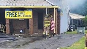 Firefighter saves flag as flames creep toward it