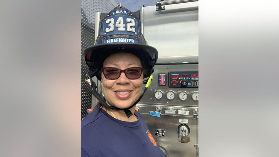 Black woman smiles. She's wearing a fire helmet, and is standing next to a fire rig.