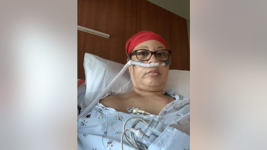 Black woman sits in hospital bed, on a machine to help her breathe.
