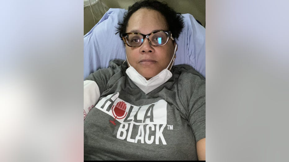 Black woman with her mask pulled down sits in an emergency department bay. She is wearing glasses, and the screen from her phone reflects the light in her glasses.