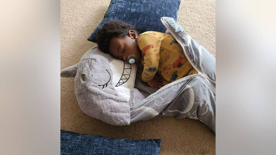 Young African American toddler sleeps on the floor, wrapped up in a shark sleeping bag. He has a pacifier in his mouth and is wearing pajamas.
