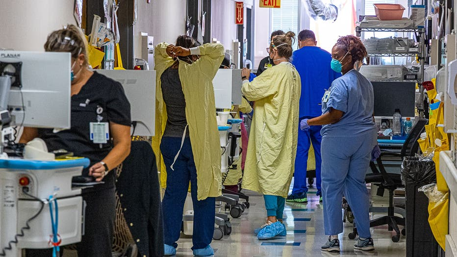 A crowded hospital hallway, where staff members wear protective equipment like masks and gowns