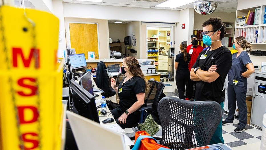 ER staff members wearing masks and scrubs look at computer monitors.
