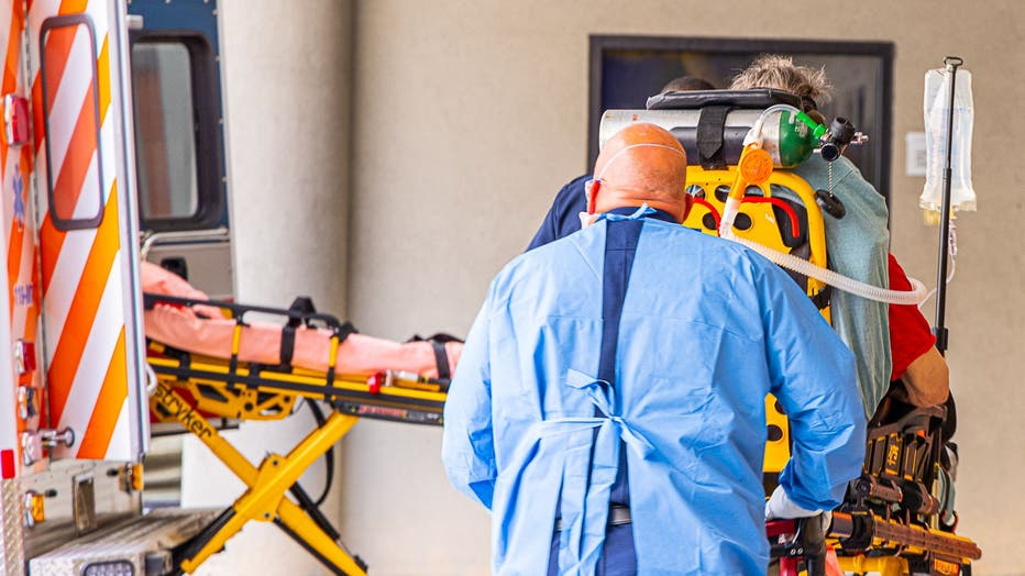 A hospital staffer wearing a protective gown pushes a patient on a gurney outside the emergency department.