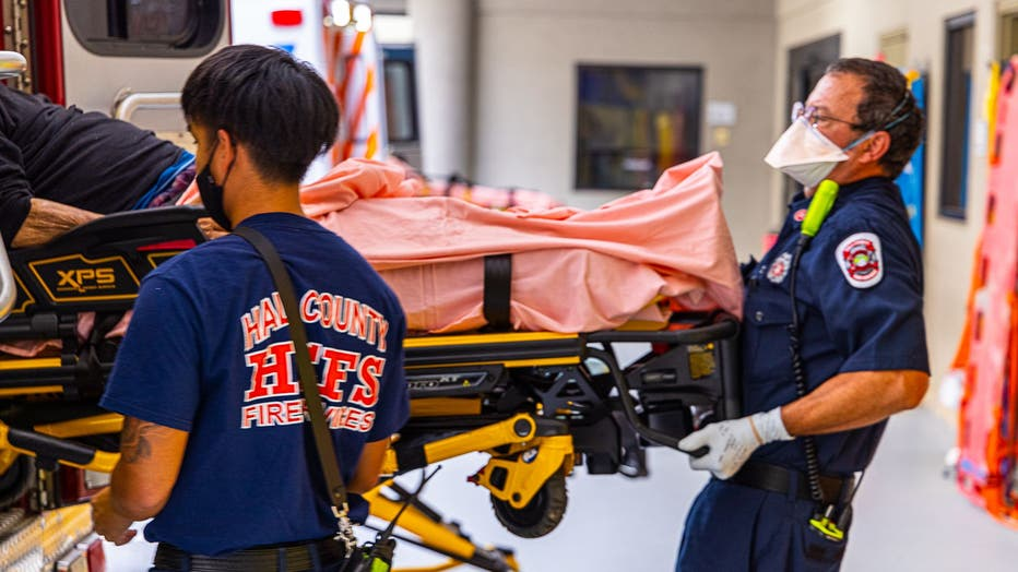 A patient is unloaded from an ambulance