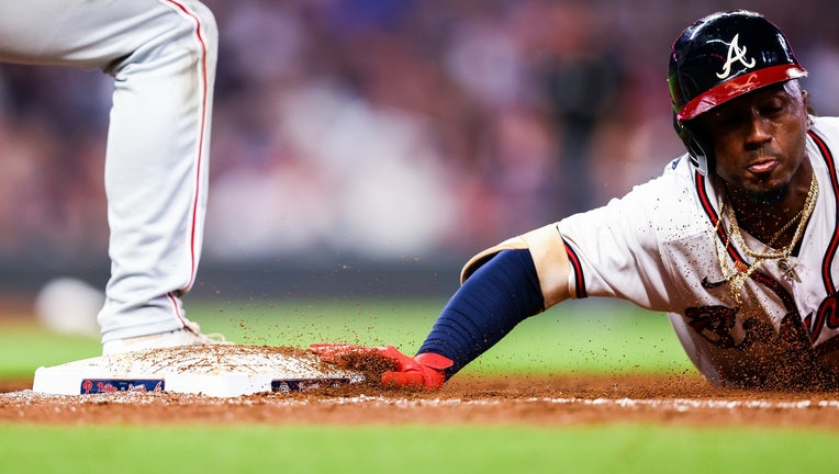 Ozzie Albies #1 of the Atlanta Braves dives back to first base on a pickoff attempt during game 2 of a series between the Atlanta Braves and the Philadelphia Phillies at Truist Park on September 29, 2021 in Atlanta, Georgia. (Photo by Casey Sykes/Getty Images)