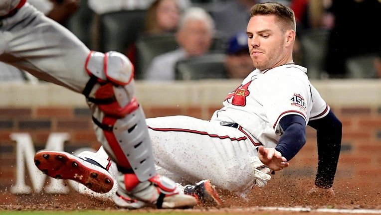 Freddie Freeman #5 of the Atlanta Braves slides safely into home on a triple hit by Ozzie Albies (not shown) during the fifth inning against the Philadelphia Phillies at Truist Park on September 30, 2021 in Atlanta, Georgia. (Photo by Adam Hagy/Getty Images)